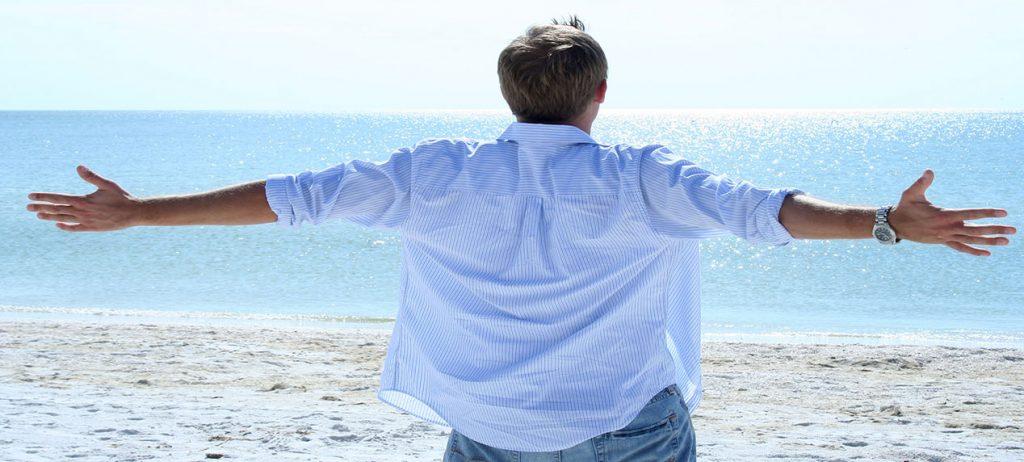 Comme appris avec son sophrologue, Un homme respire profondément, bras ouverts face à la mer -